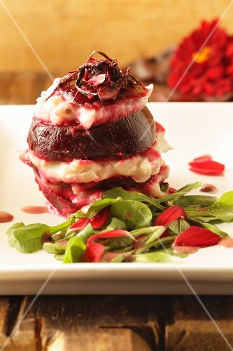 A beetroot salad with white bean cream on a bed of wild herb salad