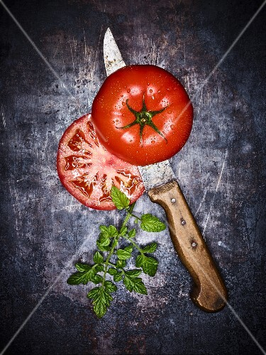 A beef tomato sliced in half with a knife on a grey surface (seen from above)
