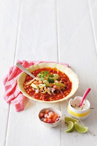 Spicy bean soup with avocado, cheese and tortilla strips