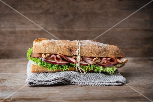 A baguette with Serrano ham, walnut, apple and frisee lettuce