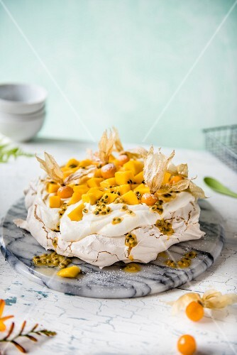 Pavlova with cream, mango, passion fruit and physalis