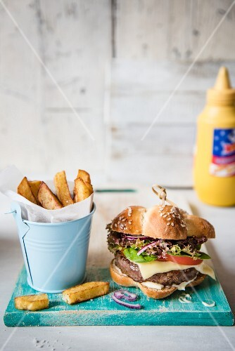 A cheeseburger with chips in front of a bottle of mustard