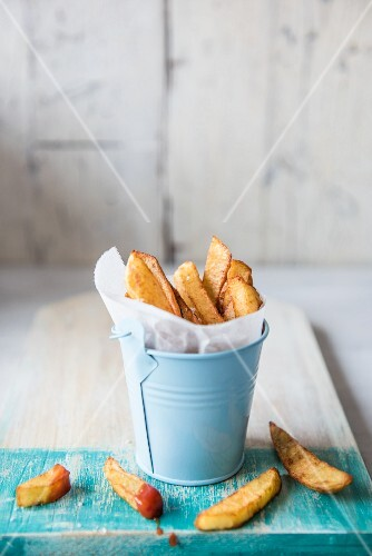 Chips in a small blue metal bucket with ketchup