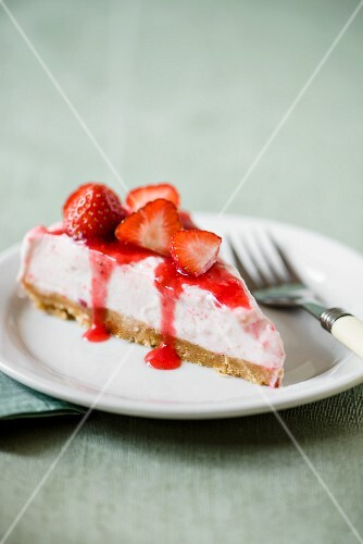 A slice of strawberry cheesecake on a plate with a fork