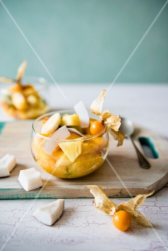 Exotic fruit salad with mango, coconut, pineapple, banana, orange and kiwi in a glass bowl