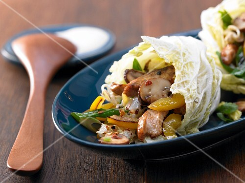 Hot Chinese cabbage wraps with turkey strips, peppers and mushrooms