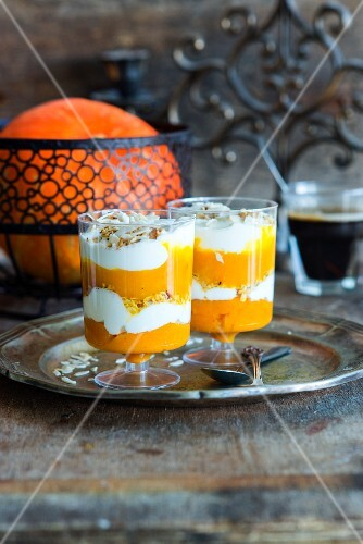 Layred dessert with pumpkin puree, yoghurt and muesli in two glasses