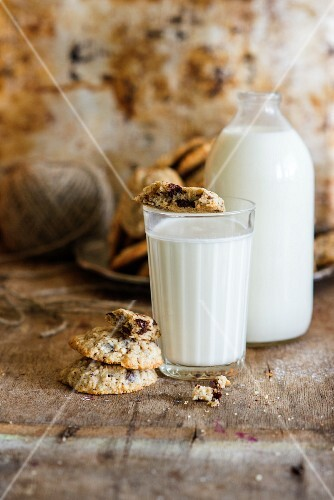 A glass and a bottle of milk and oat biscuits with chocolate chips