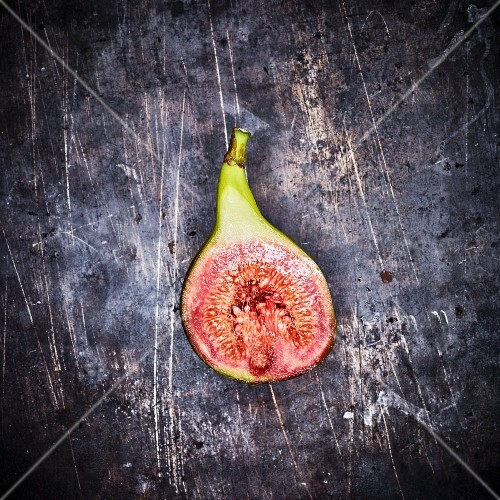 Half a red fig on a metal surface (seen from above)