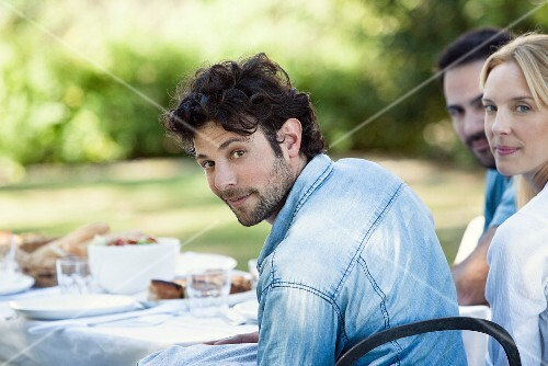 A man enjoying a meal outdoors with friends