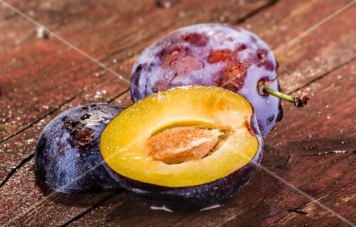 Whole and halved plums on a wooden surface
