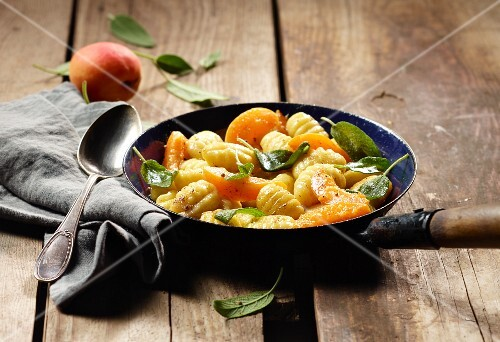 Gnocchi with apricots and sage in a frying pan