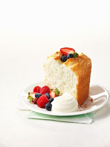 A slice of angel food cake with berries and cream