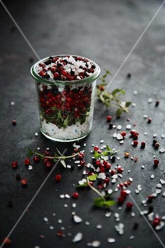 Sea salt, red pepper, black pepper and herbs in a glass