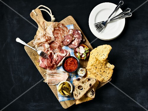 A charcuterie platter with bread, radishes and gherkins (seen from above)