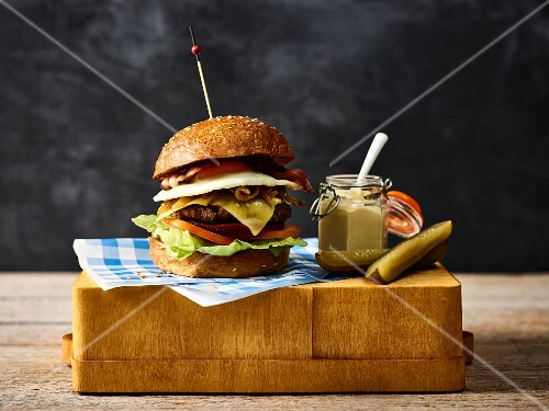 A cheeseburger with mustard and gherkins