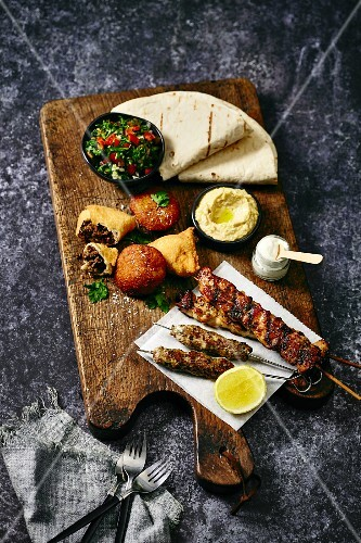 A Middle Eastern platter with kofta, tabbouleh, hummus and flatbread