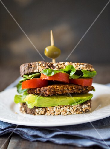 A vegan burger sandwich on wholemeal sourdough bread with avocado and tomato