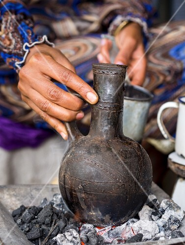 A woman brewing coffee in a jebena (a clay coffee pot) during a traditional Ethiopian coffee ceremony