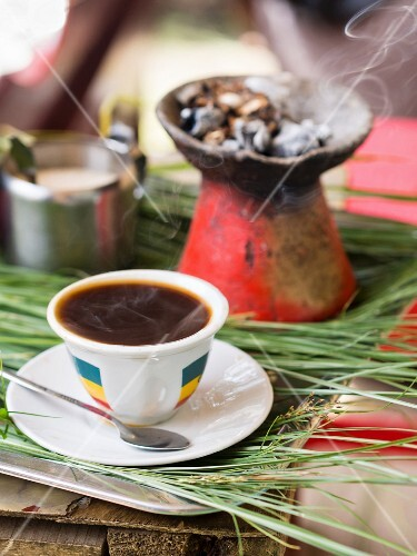 A cup of Ethiopian coffee served with incense at a traditional Ethiopian coffee ceremony