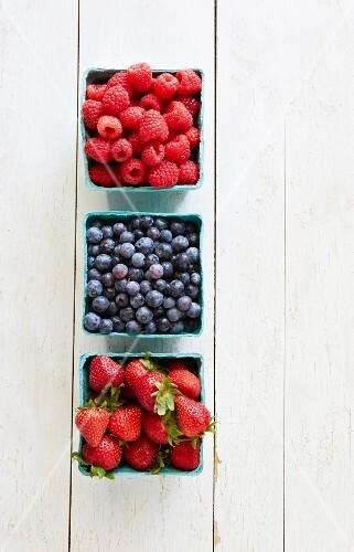 Raspberries, blueberries and strawberries in cardboard punnets