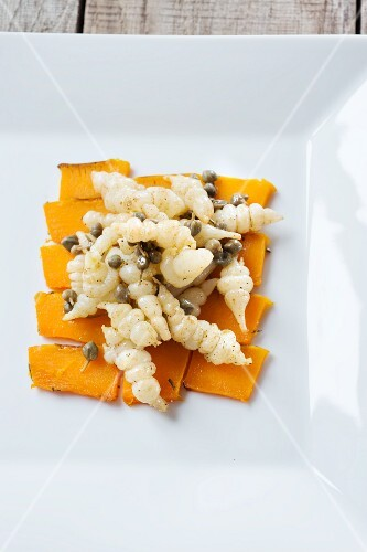 Lukewarm Japanese artichoke salad with capers on a bed of pumpkin