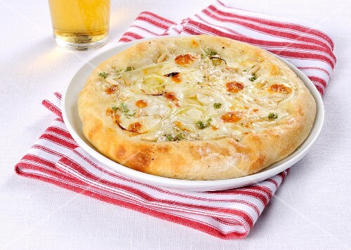 A small onion pizza with Taleggio cheese and pine nues