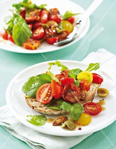 Tomato salad with roasted garlic and olives on bruschetta