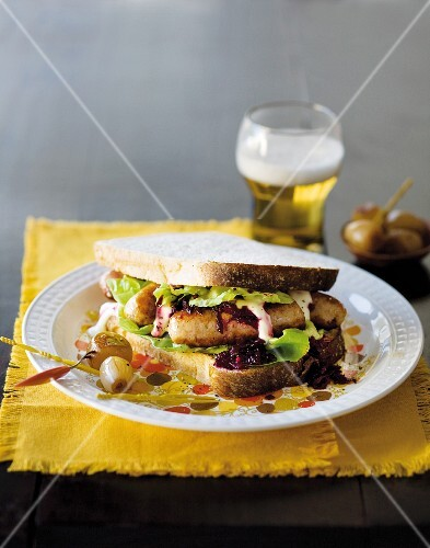 A sandwich with pork sausages and beetroot relish