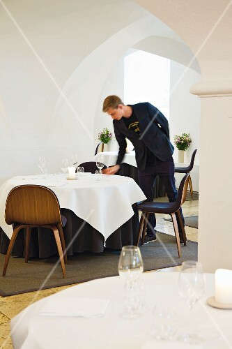 A head waiter setting a table at the restaurant AOC in Copenhagen, Denmark