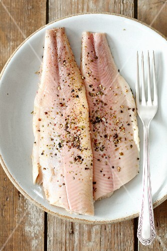 Smoked fillets of trout with pepper on a plate (seen from above)