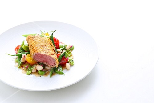 Saddle of lamb with a ciabatta coating served with a colourful bean salad