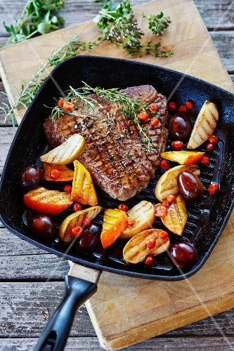 A T-bone steak wth glazed fruits and pumpkin in a grill pan