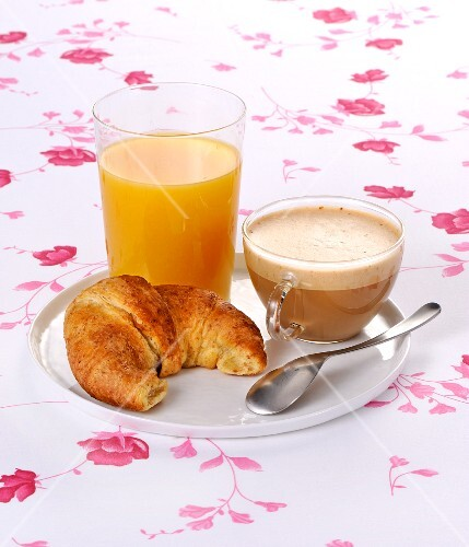 Breakfast with cappuccino, a croissant and orange