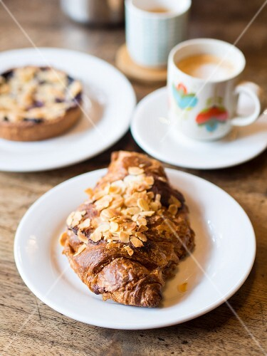 An almond croissant served with coffee in a café in France