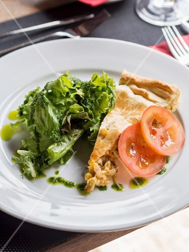 A slice of vegetable pie with mushrooms, soya and chorizo, served with salad