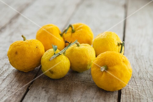 Several yuzu on a wooden surface