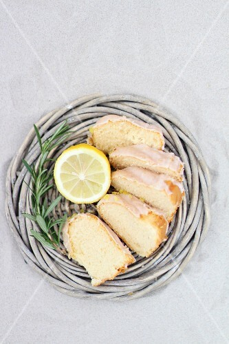 Sliced Bundt cake in a wicker basket with lemon and rosemary