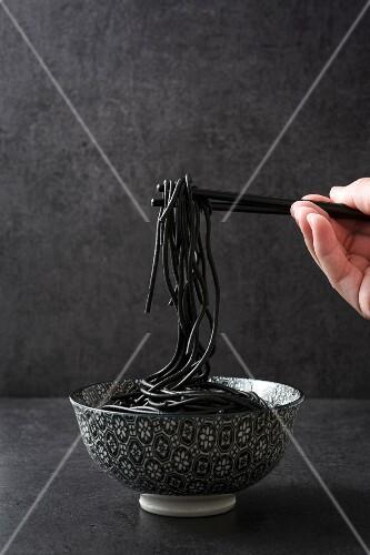 Black spaghetti hanging from chopsticks
