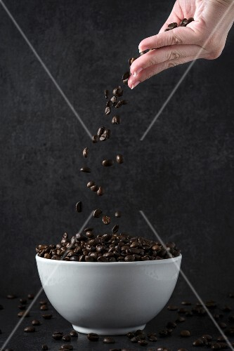 A hand throwing coffee beans into a bowl