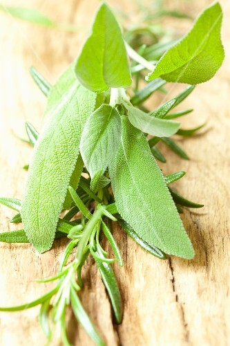 Fresh sage and rosemary on a wooden surface