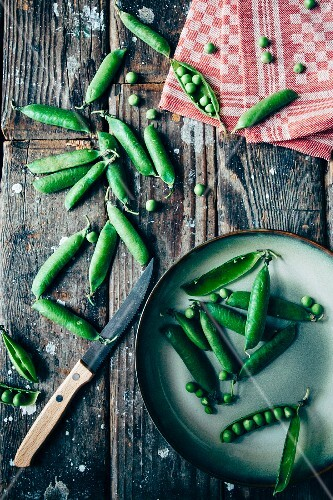 Fresh peas and pods on a wooden surface