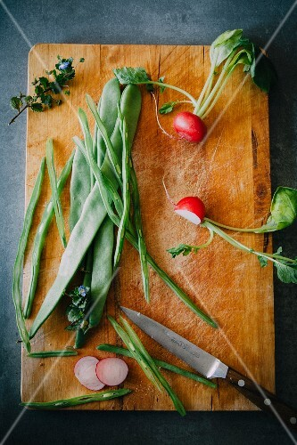 Radishes and green beans on a chopping board