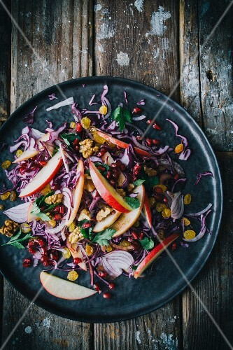 Red cabbage salad with red onion, apple wedges, parsley, sultanas, walnuts and pomegranate seeds