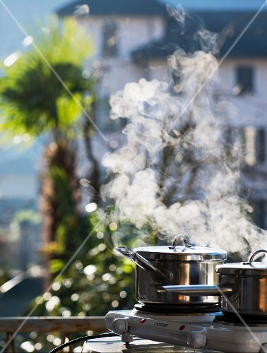Cooking outside in winter: steaming saucepan on a hob