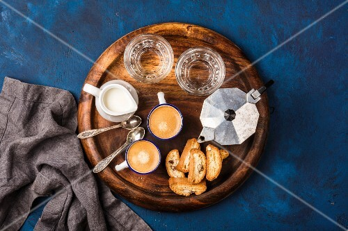 Coffee espresso in cups with italian cantucci, cookies and milk in jug on wooden serving round board