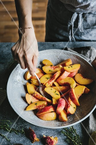 A Woman is mixing sugar sprinkled peaches