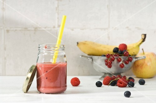 Fruit smoothie in a glass with assorted fruits in a bowl