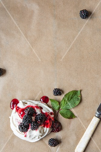 A meringue with whipped cream and blackberry sauce (seen from above)