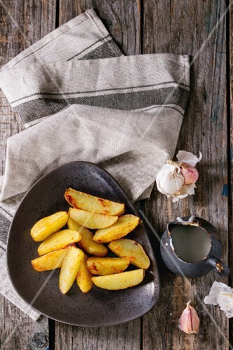 Fried country potatoes on brown ceramic plate, served with homemade aioli sauce in jug